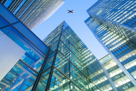 Foto de A jet airplane silhouette with business office towers background - Imagen libre de derechos