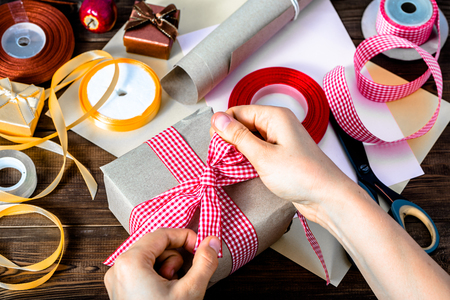 Foto de Wrapping christmas present with gray paper and ribbons. Hands making bow on gift. - Imagen libre de derechos
