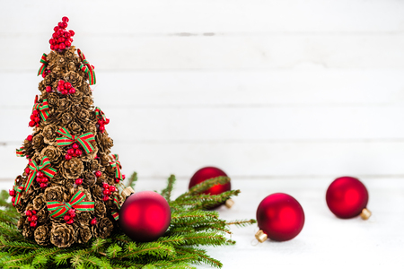 Foto de Christmas background with decorations - red balls and fir twigs on white wooden table - Imagen libre de derechos
