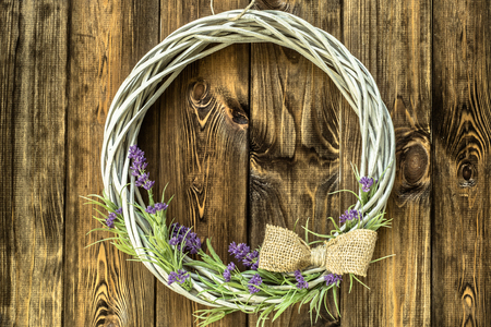 Photo pour Braided wicker wreath with lavender flowers on wooden rustic background. Provencal style. - image libre de droit