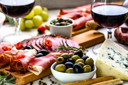 Foto de Variety food on table, wine snack set, olives, cheese and other appetizer, italian antipasti on plate - Imagen libre de derechos