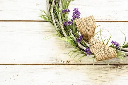 Foto de Braided wicker wreath with lavender flowers on vintage wood background. Provencal style. - Imagen libre de derechos