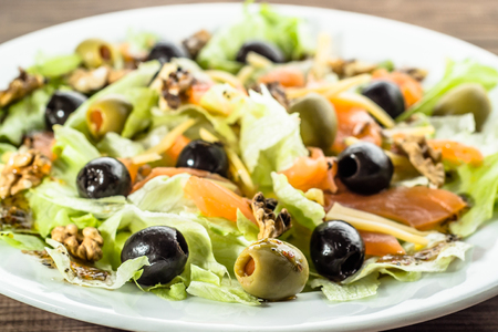 Photo for Mediterranean salad with vegetables, lettuce, salmon and olives, healthy diet concept - Royalty Free Image