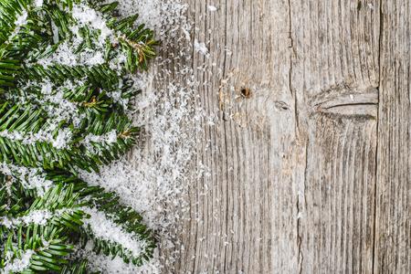 Foto de Christmas border with fir branches and snowflakes on wooden background - Imagen libre de derechos