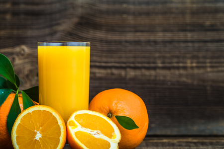 Photo pour Freshly squeezed orange juice and fresh oranges on wooden table - image libre de droit