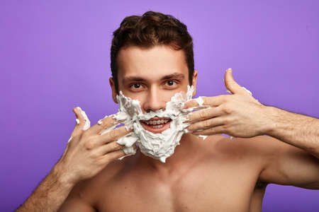 Photo for comic positive man with hands on his cheeks applying shaving foam, close up portrait. - Royalty Free Image
