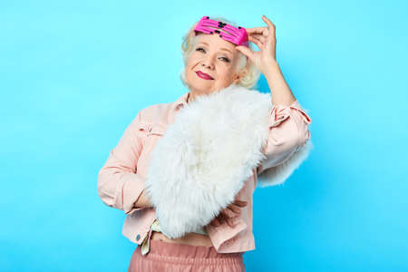Foto de trendy pretty senior lady in fashionable clothes with funny glasses on her forehead posing to the camera. isolated blue background. - Imagen libre de derechos