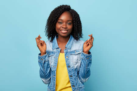 Foto de cheerful smiling American girl has joyful expressions, cross fingers and smile gladfully, wear casual trendy clothes, isolated over blue wall.gesture, body language concept - Imagen libre de derechos
