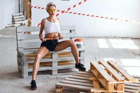 Foto de erotic hot girl in top and shorts, with wide open legs sitting, holding a building instrument. full length photo - Imagen libre de derechos