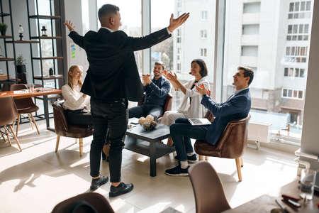 Foto de Photo of successful businessman raising his arms expressing positive feeling and emotion, back view photo. happiness, celebration - Imagen libre de derechos