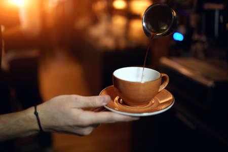 Foto de preparation method. guy pouring cold brew coffee, close up cropped photo, latte falling into cup, man going to have breakfast - Imagen libre de derechos
