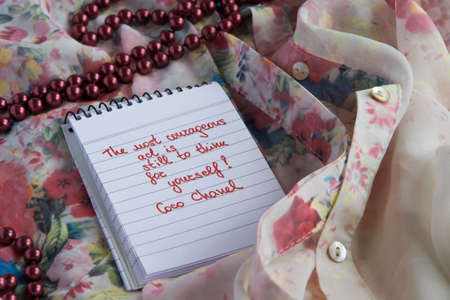 Photo for Coco Chanel quotes written on a block note, pearl accessories and  and silky flower shirt ,inspiration phrase The most courageous act is still to think for yourself - Royalty Free Image