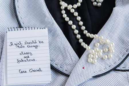 Photo for Coco Chanel quotes written on a block note, pearl accessories and a classy jacket ,inspiration phrase A girl should be two things: classy and fabulous - Royalty Free Image