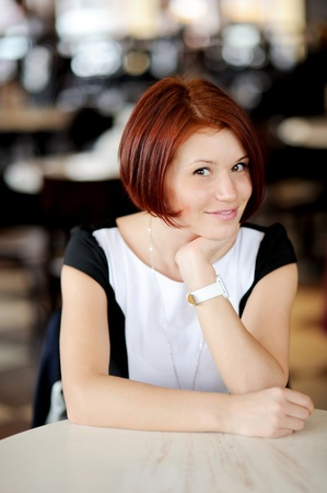 Portrait of beautiful woman with red hair sitting at a table
