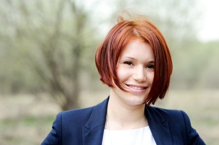 Portrait of beautiful woman with red hair posing outdoors