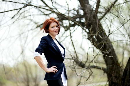Beautiful woman with red hair in business suit posing outdoors