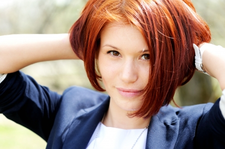 Close-up portrait of beautiful woman with red hair posing outdoors