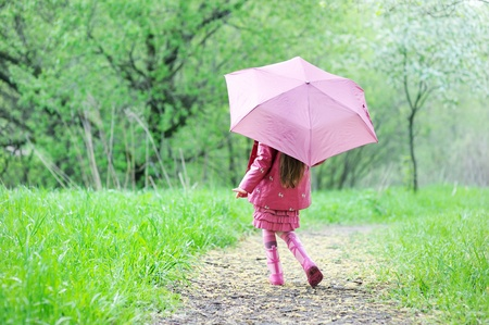 Kid girl in a raincoat walking outdoors with pink umbrella