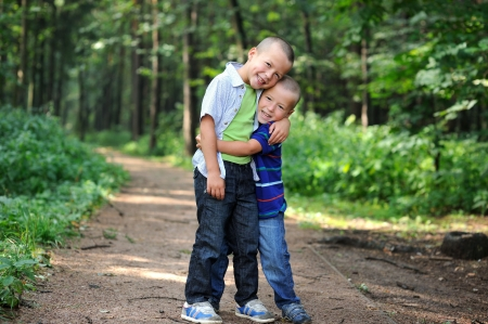 Outdoor portrait of brothers standing together in the forest