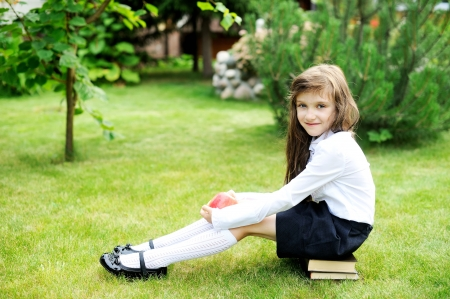 Photo pour Young girl in school uniform sitting on stack of books - image libre de droit