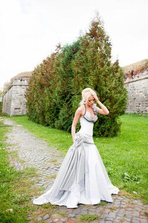 Foto de Beautiful bride after wedding ceremony walking near old palace - Imagen libre de derechos