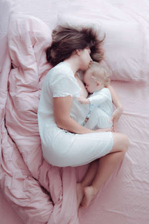 Photo pour A young mother breastfeeds her baby lying in a pink bed. Hugs his. Sleeping - image libre de droit