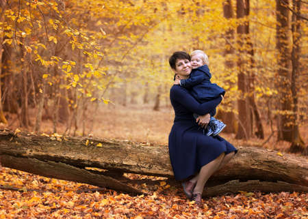 Foto de Mother and little daughter in blue dresses sitting on a fallen tree in a yellow autumn forest - Imagen libre de derechos