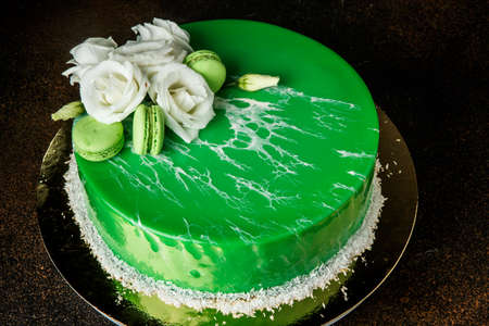 Photo pour glazed mousse green cake decorated with white roses and mint macaroons - image libre de droit