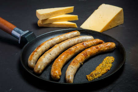Photo for large frying pan with fried thin meat sausages and granular mustard served with sliced hard cheese on black background - Royalty Free Image