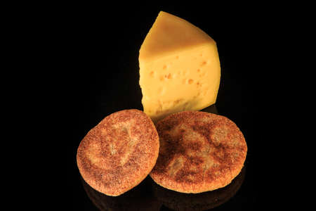 Photo for top view of hard porous yellow cheese piece served with two rye flapjacks on black mirror background with reflection - Royalty Free Image