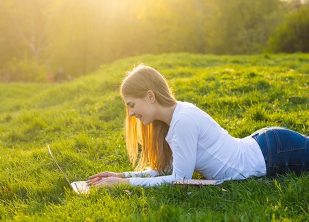 Foto de Young beautiful female student with long blond hair lies with a laptop on the grass in spring in sunset. - Imagen libre de derechos
