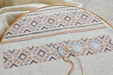 Foto de Embroidered fragment on flax by brown and beige cotton threads. Macro embroidery texture flat stitch. Ukrainian ethnic ornament. - Imagen libre de derechos