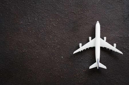 Photo pour Miniature airplane on a dark background. Travel concept. Flat lay with copy space. - image libre de droit