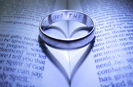 Photo pour Engraved wedding band making heart shadow on open Bible - image libre de droit