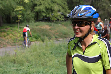 The woman-cyclist in a dark blue helmet and black glasses smiles