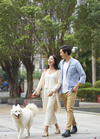 Foto de Asian couple laughing while walking dog outdoor in garden - Imagen libre de derechos