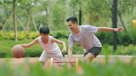 Foto de Asian father playing basketball with son - Imagen libre de derechos