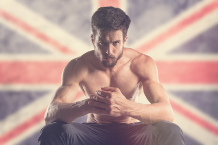 Photo for Muscular man with Union Jack Flag behind - Royalty Free Image