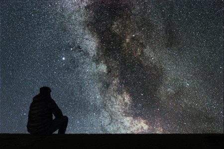 Photo pour Milky Way. Night sky with stars and silhouette alone man looking at starry sky. - image libre de droit