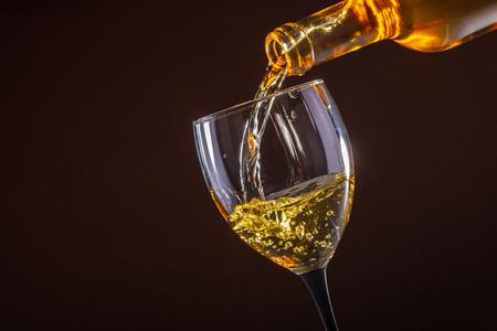 Foto de white wine pouring glass on brown background - Imagen libre de derechos