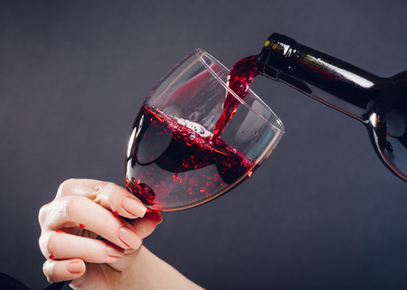 Photo for red wine pouring glass on black background - Royalty Free Image