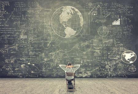 Photo pour Businessman sitting on a chair and studying math formulas on blackboard - image libre de droit