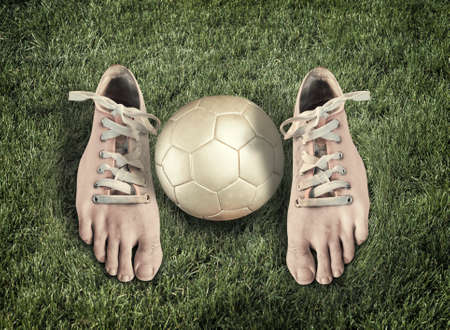 Pair of shoes looking like real legs and a soccer ball on green grass