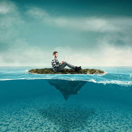 Foto de Business man work on laptop sitting on a piece of land floating in the ocean.  Split half-water seascape. - Imagen libre de derechos