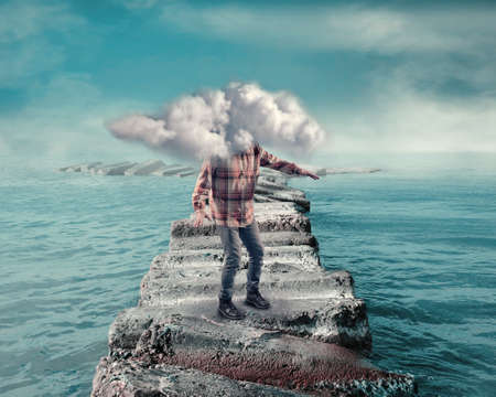 Photo for Young man covered by a cloud walking on a pontoon of rocks in the ocean. - Royalty Free Image