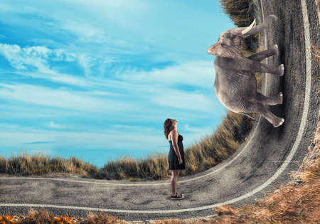 Photo pour Young girl looking to an elephant going up on a bend road. - image libre de droit