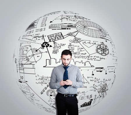 Businessman using a smartphone against a white wall drawn with strategies and formulas.