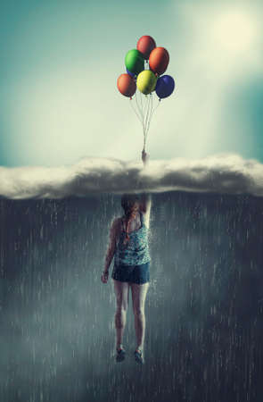 Foto de Woman flying with balloons through a rainy cloud to the sunny sky. The concept of overcoming fears. - Imagen libre de derechos
