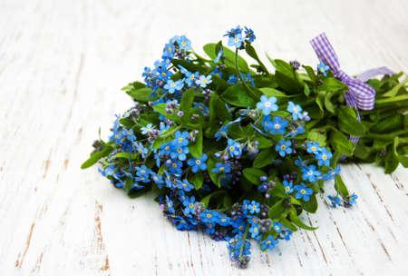 Photo pour Forget-me-nots flowers with ribbon on a wooden background - image libre de droit