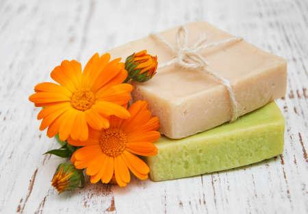 Foto de calendula flowers  and handmade bath soap on a wooden background - Imagen libre de derechos